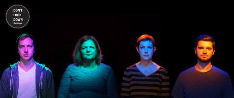 Four people on a black backdrop, looking somber.