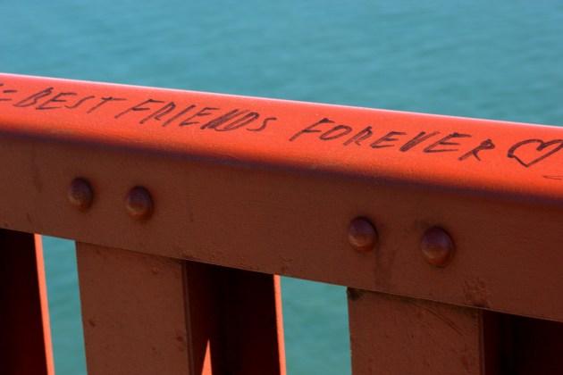 "Guard rail along the east sidewalk of the Golden Gate Bridge in San Francisco, California. A permanent marker inscription reads ""Best friends forever ?""."