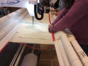 Handi Quilter longarm quilting machine loading top fabric red snapper
