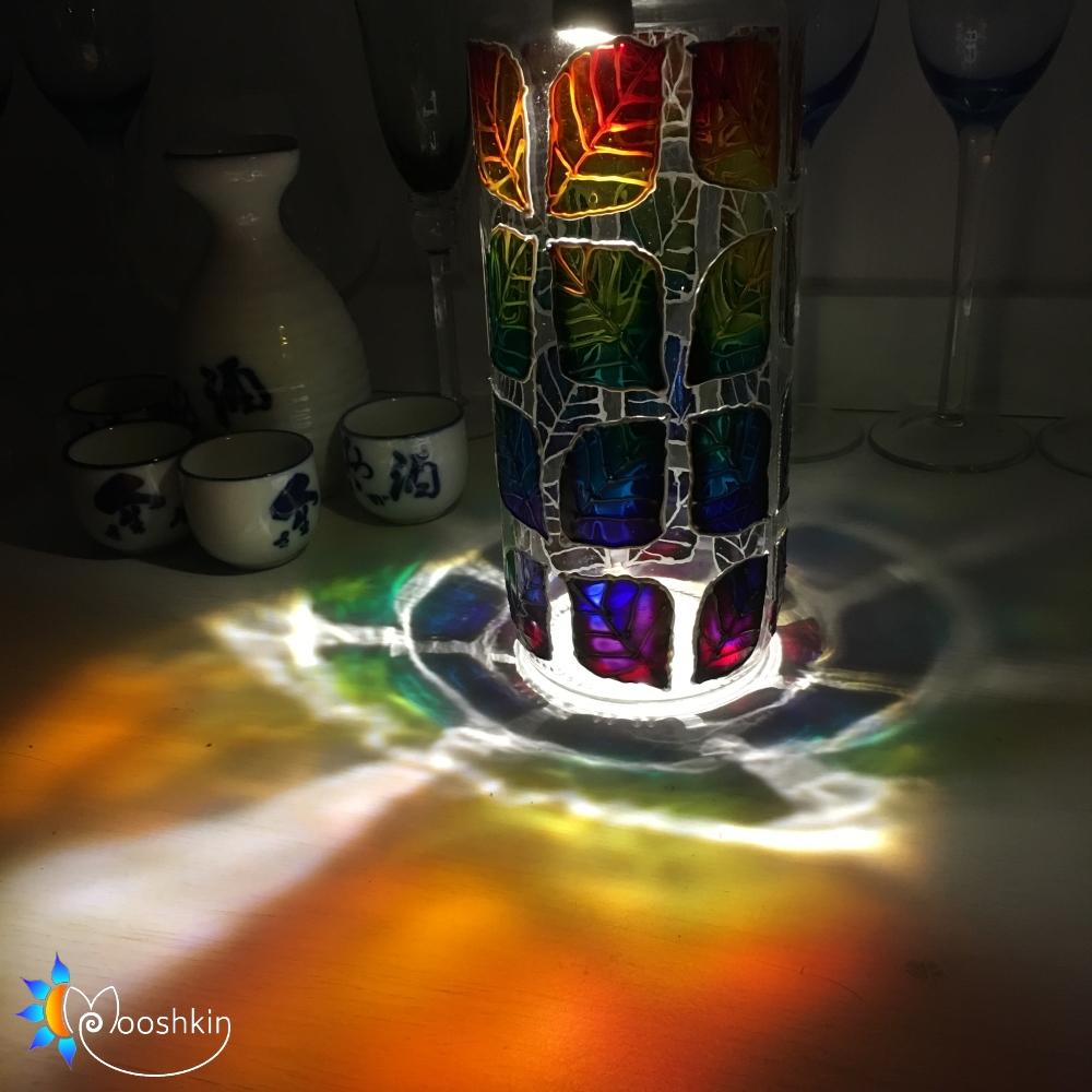 Upcycled painted hotdog jar under a lamp