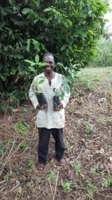 MAXWELL AWUKU HOLDING HIS MAHOGNY AND OFRAM SEEDLING
