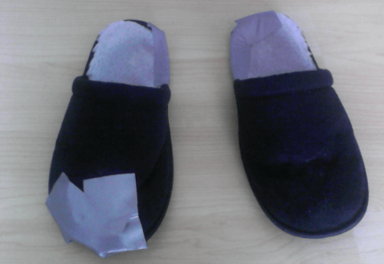 A pair of winter slippers repaired using duct tape