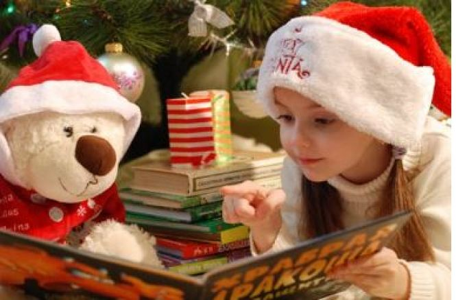 Girl reading to a Christmas bear