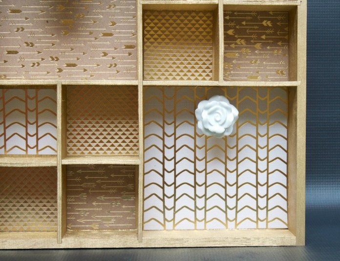 Make a fabulous golden wall organizer that features pretty decorative knobs. A great piece of wall decor that doubles as storage.