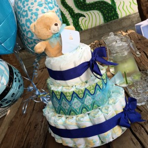 A blue and white cake made out of diapers, as a decoration and gift at a baby shower