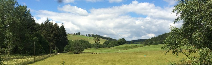 Panorama of a hillside in Scotland with blue sky above
