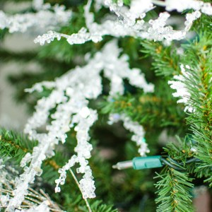 Close up picture of Christmas tree branch covered in snow