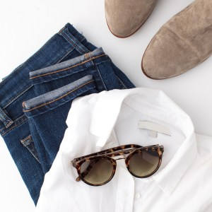 An organised pile of clothes including folded blue jeans white shirt shoes and sunglasses on a white background