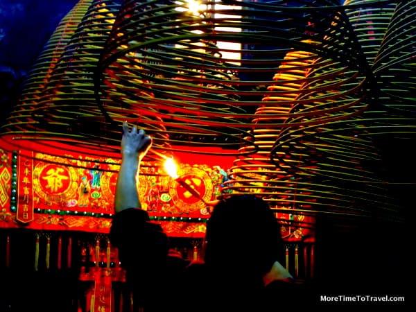 Man lighting incense coils