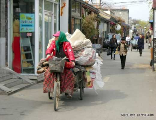 Hutong resident on tricycle transporting materials to be recycled