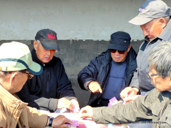 Men playing cards in a park outside the Temple of Heaven in Beijing