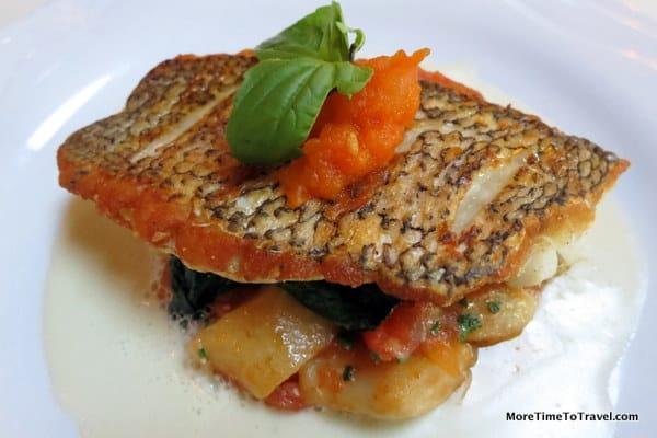 Atlantic sea bass with potato gnocchi, tomato fondue, leaf spinach and Champagne sauce