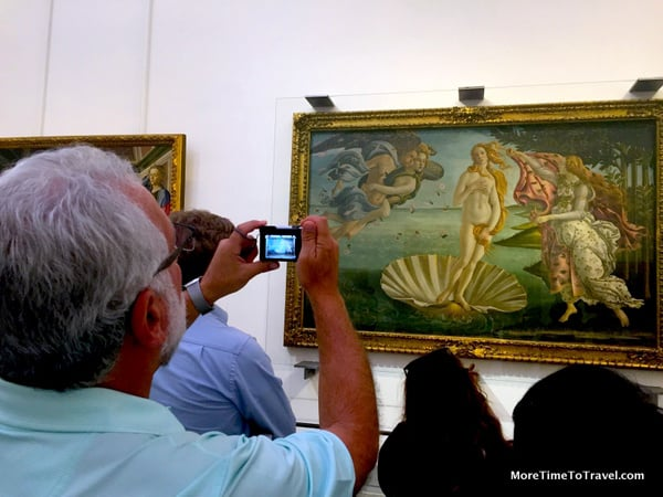 Tourist taking a photo in the Uffizi Gallery in Florence