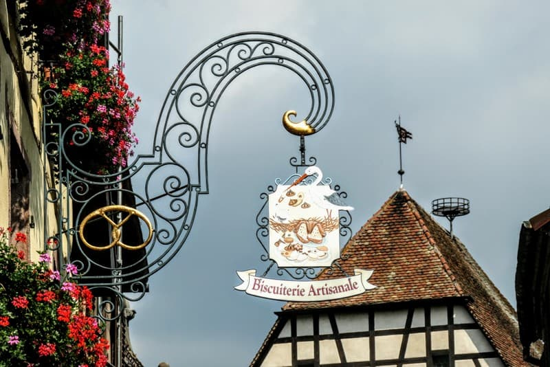 Best Road Trip from Strasbourg - One of the beautiful iron-forged signs in Kayserberg, found throughout Alsace