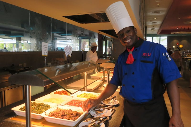 A chef proudly displays traditional Jamaican fare