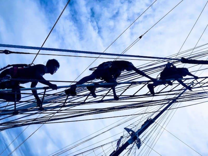 Crew members climbing the ropes