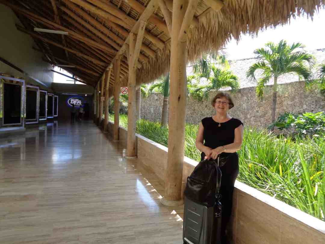 Sandra under the thatched roof of Punta Cana International Airport
