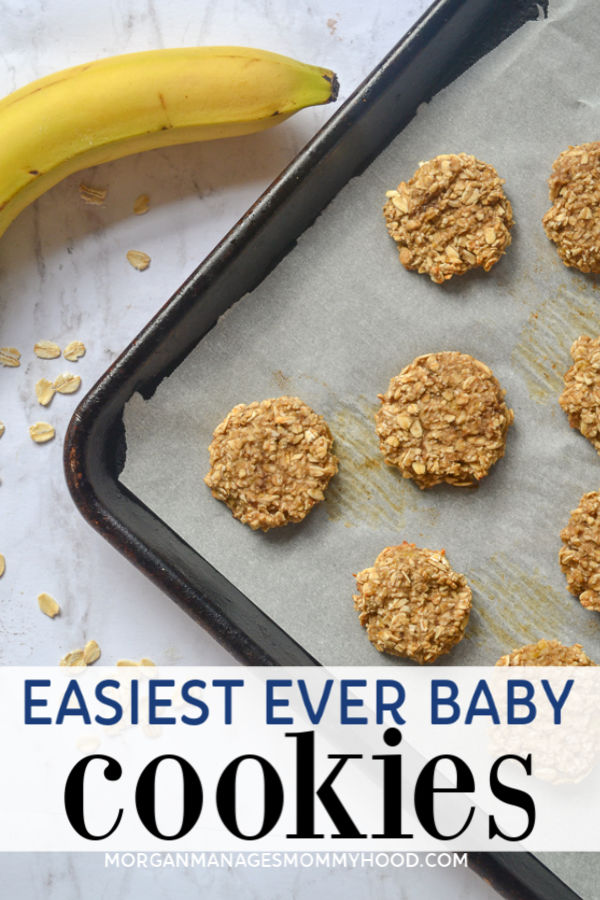 a cooking sheet lined with parchment paper and topped with simple 2 ingredient cookies on a marble counter top with a banana and oats