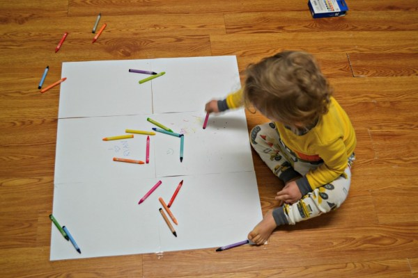 Toddler coloring on floor