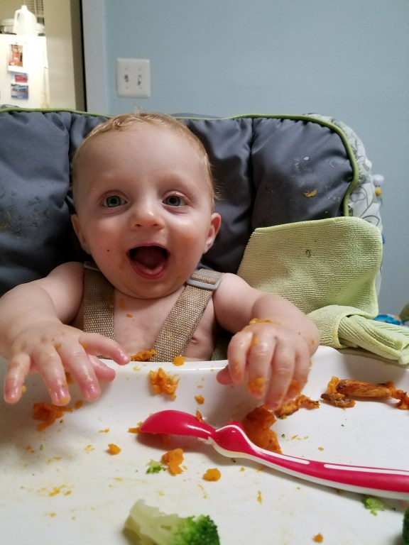 a baby in a high chair covered in food from baby led weaning with sweet potato and broccoli on the tray