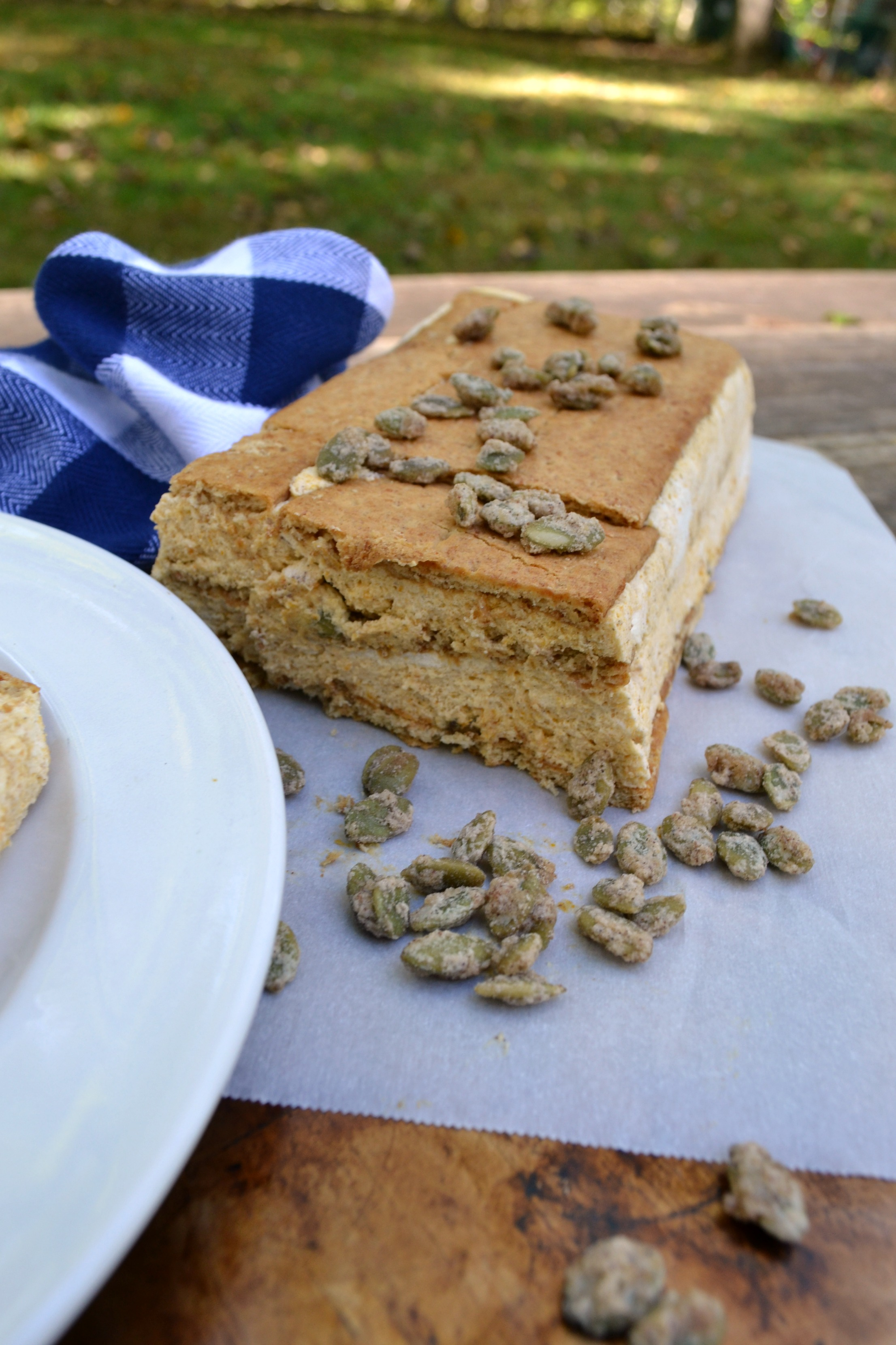 a photo of pumpkin ice box cake topped with candied pepitas on a wooden picnic table.