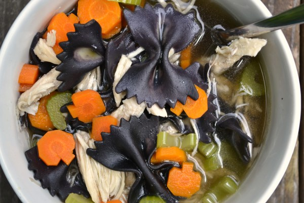 on of my favorite halloween dinners - a white bowl filled with chicken boodle soup, filled with black bat noodles and orange pumpkin carrots.