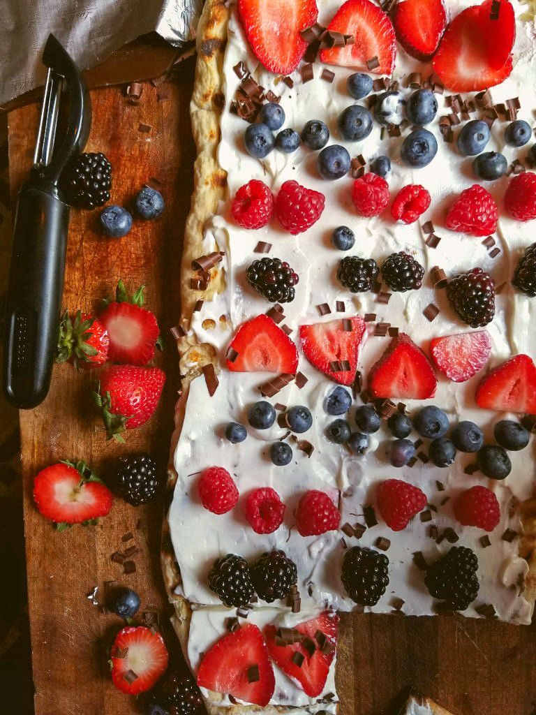 grilled dessert pizza spread with cream cheese frosting and topped with summer berries and chocolate curls