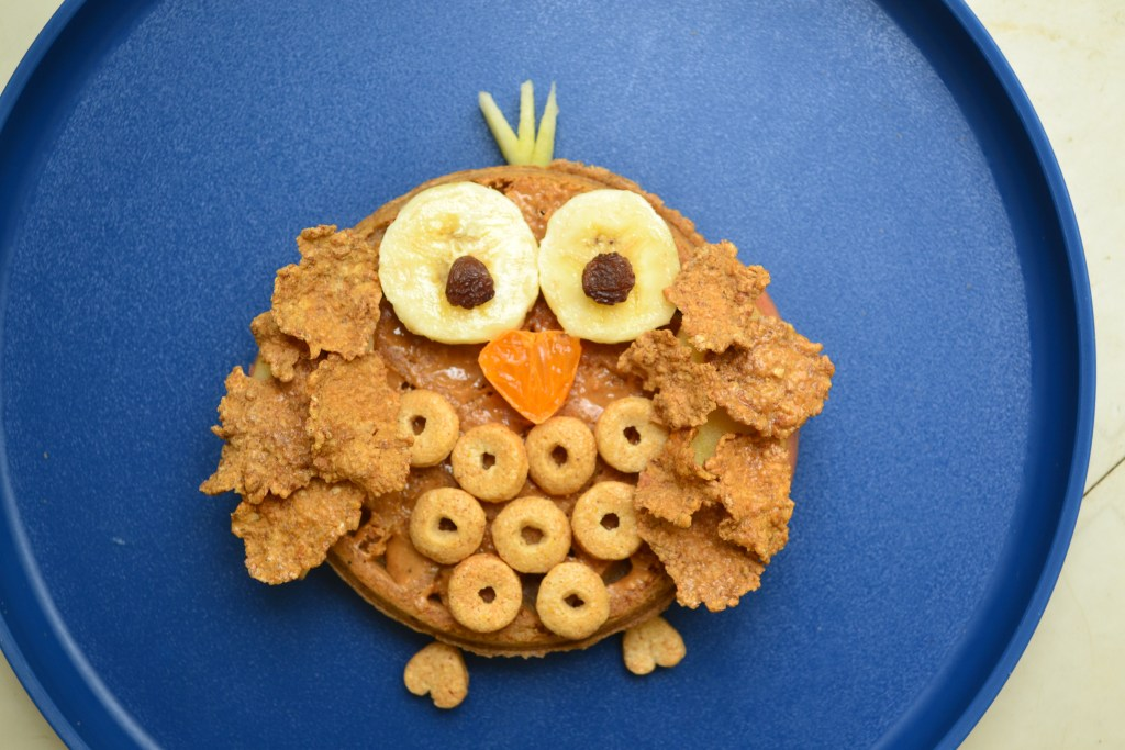 a waffle for kids that uses cereal bananas, orange and banana to make it look like an owl on a blue plate.