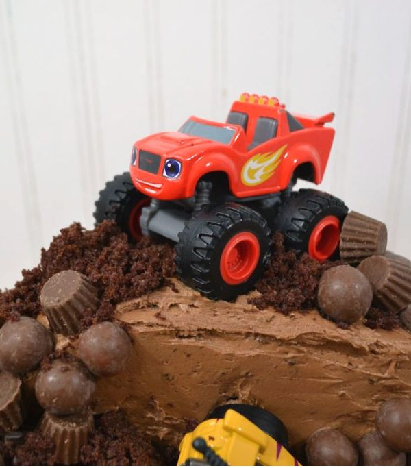 a red monster truck blaze and the monster machine toy on top of a chocolate monster truck cake.