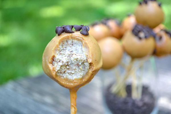 a healthy cake pop with peanut butter coating topped with mini chocolate chips and bitten open to show the soft and moist insides!
