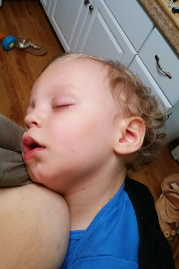 a sick toddler in sleeping in a baby carrier worn by his mom