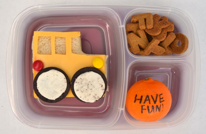 a first day of school lunch with the sandwich made to look like a school bus and a sweet note on an orange.