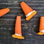 edible traffic cone using asquare cheese cracker, a carrot, and cream cheese on a wooden picnic table.