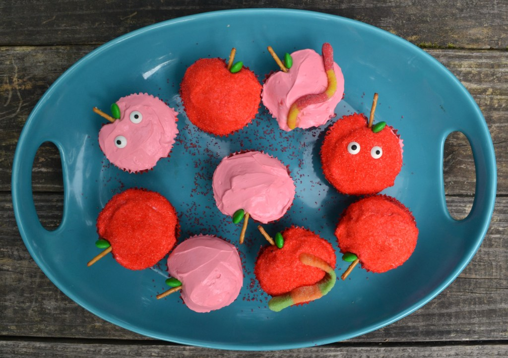 healhty apple muffins in pink and red made to look like apples on a blue platter on a wooden table