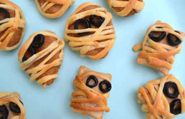 These Halloween Mummy Snacks are perfect for a Halloween party or for eating before going trick or treating. Chicken nuggets or pizza rolls wrapped in dough with olive eyes are the perfect, simple Halloween dinner!