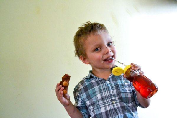 cute little boy eatting a teddy graham from a teddy bear lunch box with juice in a honey bear