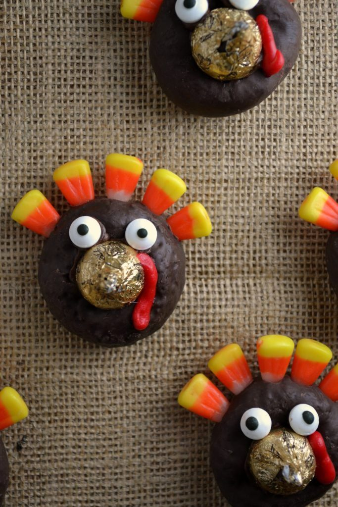 a close up of an easy turkey donut using a gold kiss, candy eyes, and candy corn feathers on a burlap background