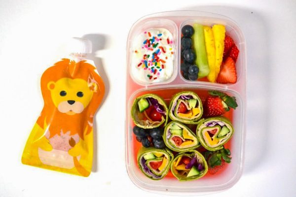 a rainbow lunch box with a rainbow wrap, fruit cutand ordered in a rainbow, and yogurt with rainbow sprinkles next to a lion squooshi pouch