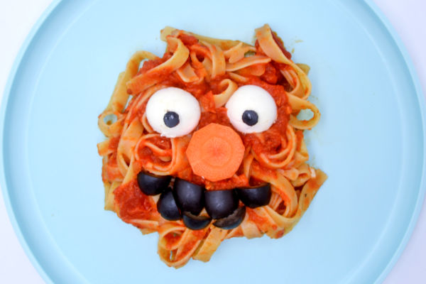 A pile of pasta covered in hidden vegetable spaghetti sauce with toppings to make it look like Elmo on a light blue plate