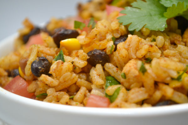 A while bowl with mexican fried rice and cilantro piled high dotted with black beans, corn, and tomato