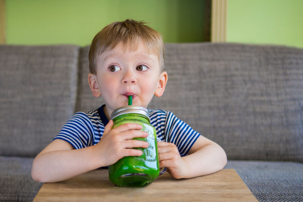 a little boy in a striped blue shirt sitting at a table drinking a green veggie smoothie from a straw in a mason jar