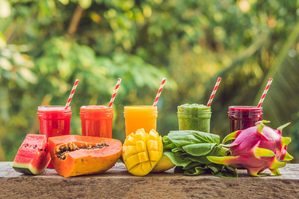 veggie smoothies in mason jars with striped straws with fresh fruits on a wooden table.