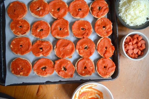 A tray line with mini bagels covered in pizza sauce to make freezer pizza bagel recipe. A bowl of cheese and a small bowl of mini pepperoni are to the side