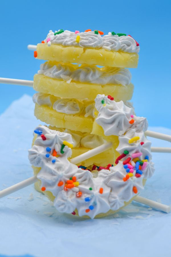 pina colada pineapple popsicles slacked with coconut cream and rainbow sprinkles, with a blue back ground on top of parhcment paper