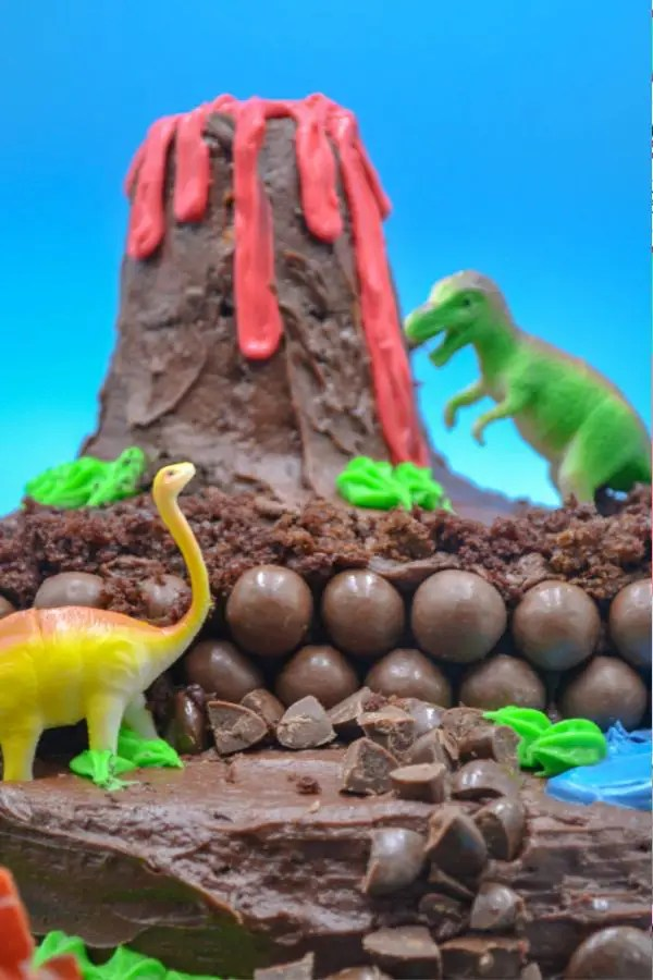 a dinosaur birthday cake with a volcano with lava and toy dinosaurs decorating it.