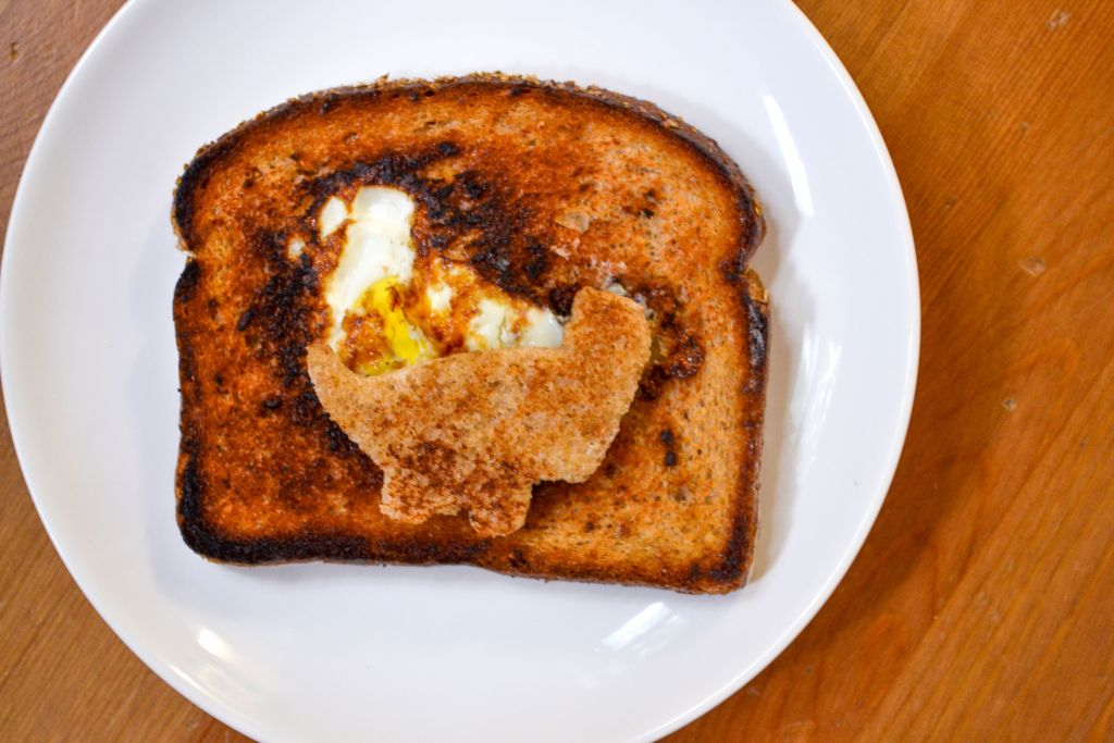 An egg in a hole made with a dinosaur cut out as the center space on a white plate.