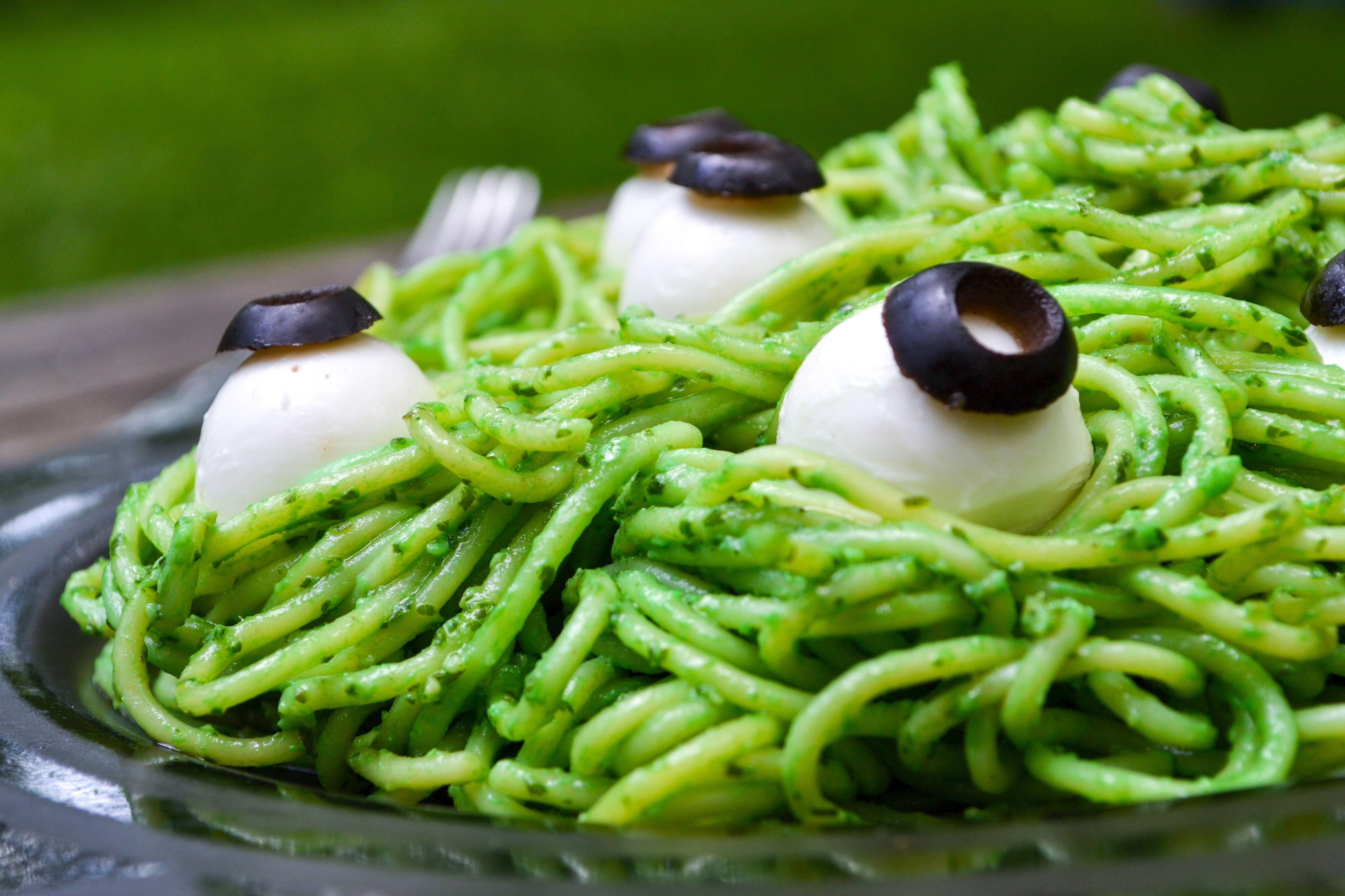 bright green spaghetti noodles covered in veggie pesto and topped with mozzarella eyeballs