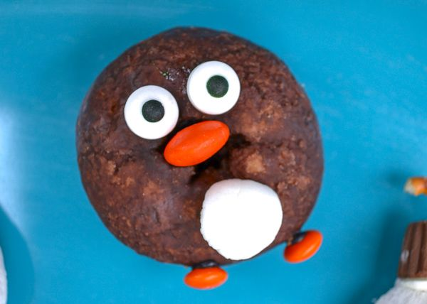 a chocolate christmas donut decorated to look like a penguin on a blue platter