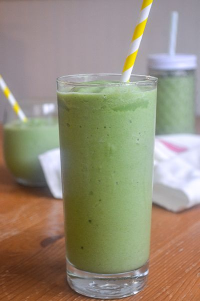 A large, tall glass filled with green spinach smoothie with a yellow striped straw