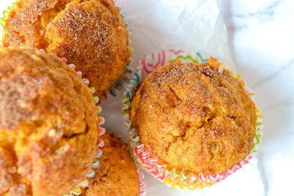 an overhead picture of sweet potato muffins with a cinnamon sugar top on parchment and marble base.